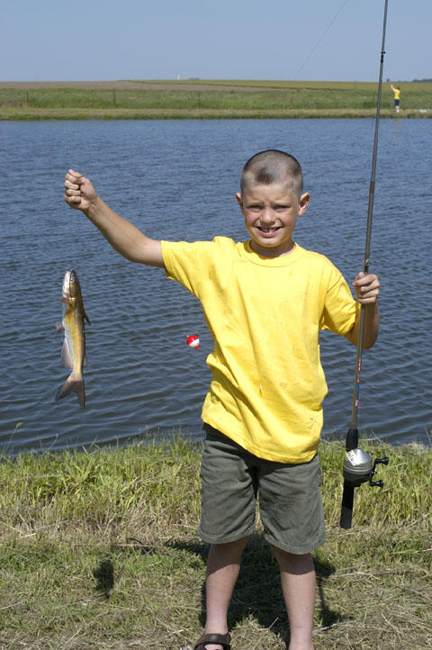 A young angler holds his latest catch