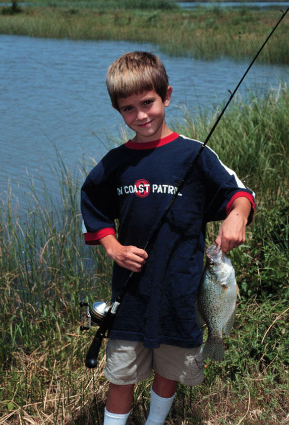 A young boy shows off his latest catch