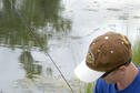 A young angler pulls a bass from the water