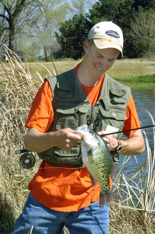 A young angler holds a crappie
