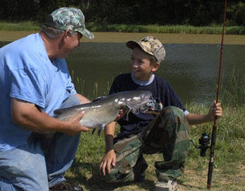 A young angler checks out his large catch: a catfish!