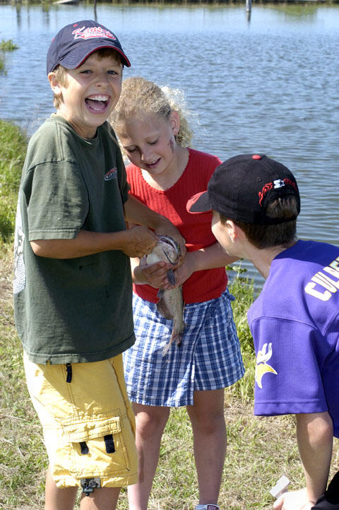 Three kids with a catfish